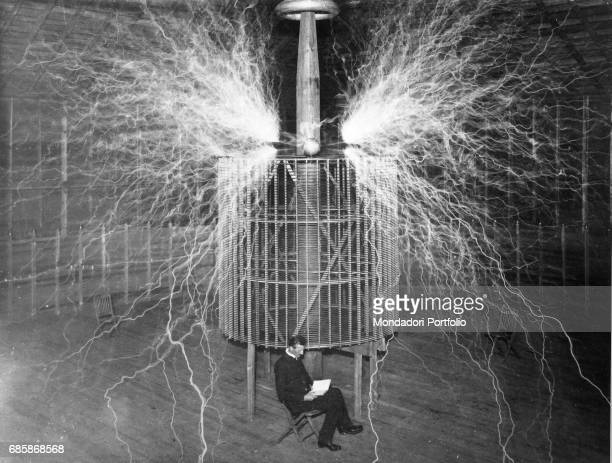Serbianborn American engineer and physicist Nikola Tesla reading a book in his laboratory next to a machine giving off electric sparks Colorado...