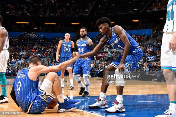 Nikola Vucevic is helped up by Jonathan Isaac of the Orlando Magic during the game against the Charlotte Hornets on February 14 2019 at Amway Center...