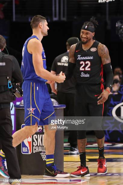 Nikola Vucevic of Team Durant and Robert Covington of the Portland Trail Blazers shake hands during the Taco Bell Skills Challenge as part of 2021...