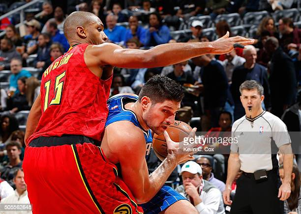 Nikola Vucevic of the Orlando Magic drives against Al Horford of the Atlanta Hawks at Philips Arena on January 18 2016 in Atlanta Georgia NOTE TO...