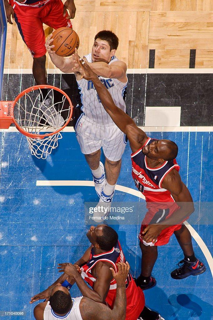 Nikola Vucevic #9 of the Orlando Magic shoots a layup against Emeka Okafor #50 of the Washington Wizards on December 19, 2012 at Amway Center in Orlando, Florida.