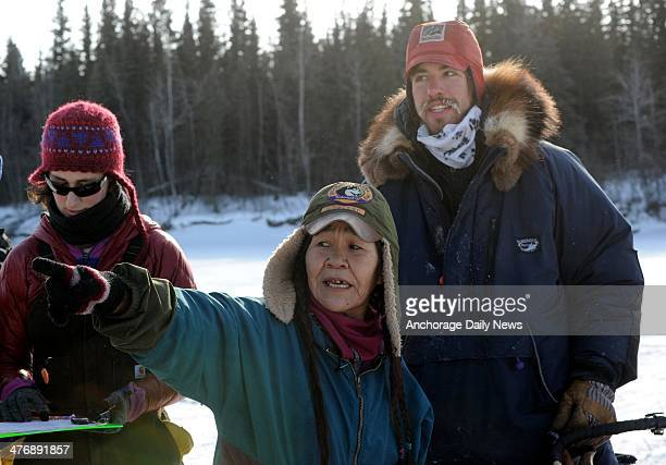 Nikolai checker Marty Runkle points out the lay of the land to musher Alex Buetow as he arrives at the Nikolai checkpoint during the 2014 Iditarod...