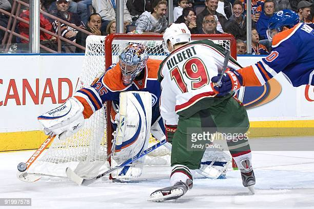 Nikolai Khabibulin of the Edmonton Oilers makes a save under pressure from Andy Hilbert of the Minnesota Wild at Rexall Place on October 16 2009 in...