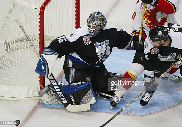Nikolai Khabibulin of the Tampa Bay Lightning eyes the puck to his right as teammate Dan Boyle defends the crease against Dave Lowry of the Calgary...