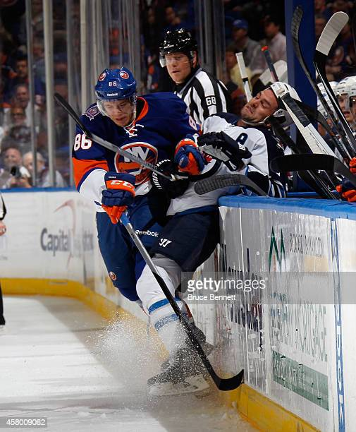 Nikolai Kulemin of the New York Islanders hits Mark Stuart of the Winnipeg Jets into the boards during the first period at the Nassau Veterans...