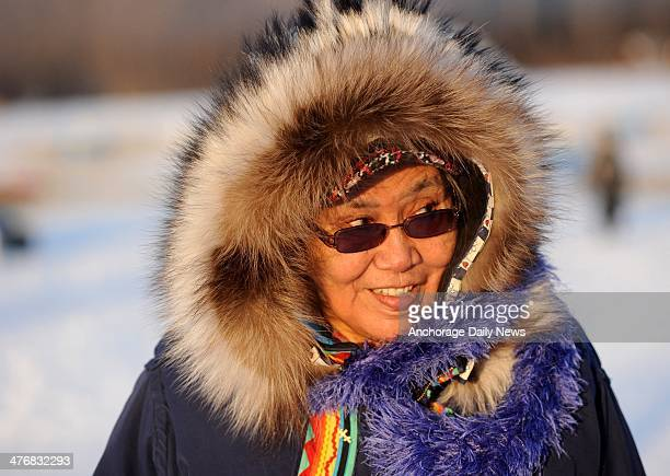 Nikolai resident Oline Petruska talks with visitors at the Nikolai checkpoint during the 2014 Iditarod Trail Sled Dog Race at sunrise on Wednesday...