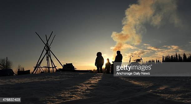 Nikolai residents Oline Petruska Tyler Alexia and Stephanie Petruska wait by the wood fired hot water for mushers to come in at the Nikolai...