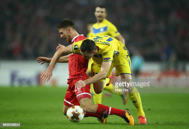Nikolai Signevich of FC Bate Borisov and Salih Oezcan of FC Koeln battle for posession during the UEFA Europa League group H match between 1 FC Koeln...