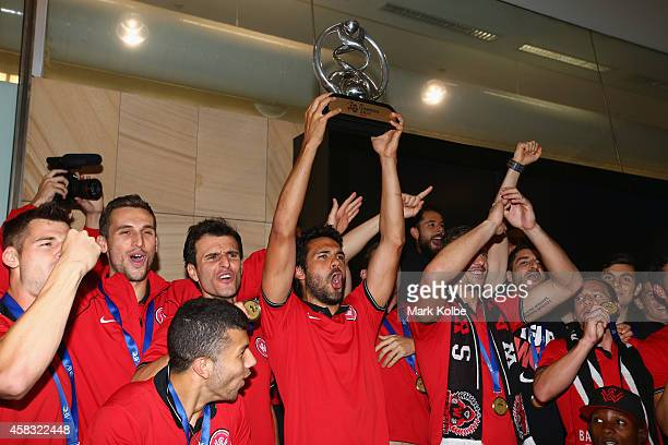 Nikolai Topor-Stanley of the Western Sydney Wanderers holds aloft the trophy as the team celebrates on arrival at Sydney International Airport from...