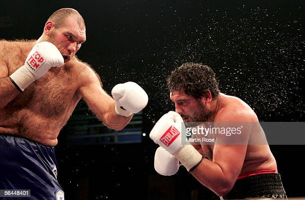 Nikolai Valuev of Russia hits John Ruiz of USA with a left punch during their WBA Heavyweight Fight at the Max-Schmeling Hall on December 17, 2005 in...