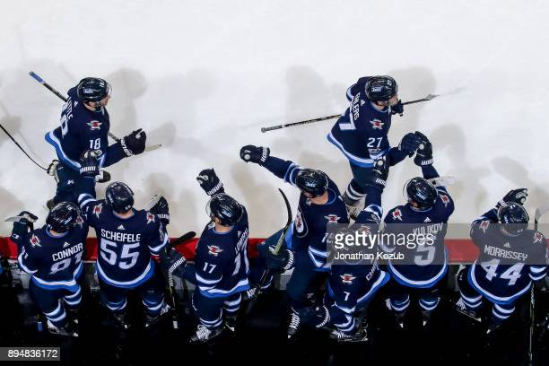 Nikolaj Ehlers and Bryan Little of the Winnipeg Jets celebrate a second period goal against the Vancouver Canucks with teammates at the bench at the...