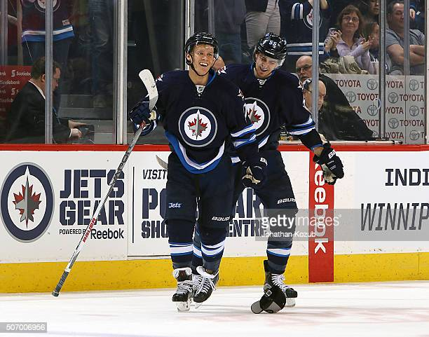 Nikolaj Ehlers and Mark Scheifele of the Winnipeg Jets are all smiles as they skate to the bench following Ehler's first career hat trick during...