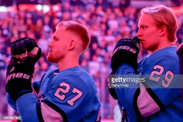 Nikolaj Ehlers and Patrik Laine of the Winnipeg Jets stand on the bench during the singing of 'O Canada' prior to NHL action against the Buffalo...