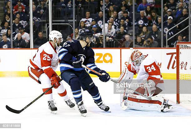 Nikolaj Ehlers of the Winnipeg Jets and Mike Green of the Detroit Red Wings watch as goaltender Petr Mrazek makes a pad save during third period...