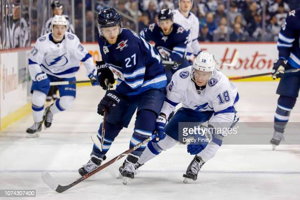 Nikolaj Ehlers of the Winnipeg Jets and Ondrej Palat of the Tampa Bay Lightning follow the play down the ice during third period action at the Bell...