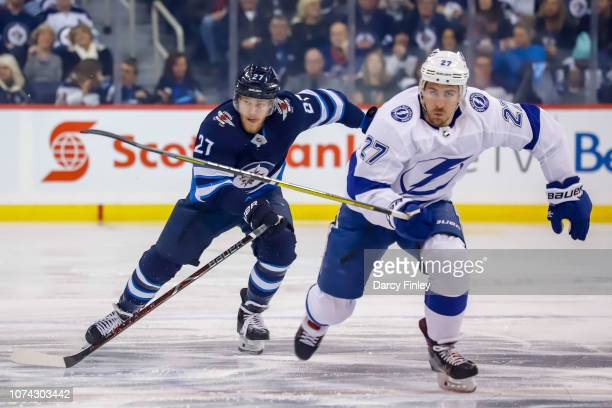 Nikolaj Ehlers of the Winnipeg Jets and Ryan McDonagh of the Tampa Bay Lightning follow the play down the ice during first period action at the Bell...