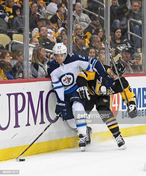 Nikolaj Ehlers of the Winnipeg Jets battles for a puck along the boards with Chad Ruhwedel of the Pittsburgh Penguins in the third period during the...