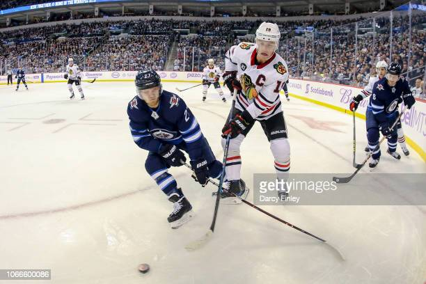 Nikolaj Ehlers of the Winnipeg Jets battles Jonathan Toews of the Chicago Blackhawks for the puck along the boards during first period action at the...