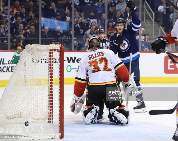 Nikolaj Ehlers of the Winnipeg Jets celebrates after teammate Paul Stastny deflects the puck past goaltender Jon Gillies of the Calgary Flames for a...