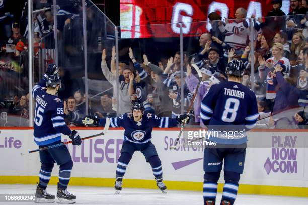 Nikolaj Ehlers of the Winnipeg Jets celebrates his third period goal against the Chicago Blackhawks with teammates Mark Scheifele and Jacob Trouba at...