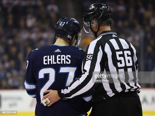 Nikolaj Ehlers of the Winnipeg Jets chats with linesman Mark Wheler during a second period stoppage in play against the Columbus Blue Jackets at the...