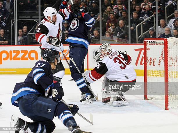 Nikolaj Ehlers of the Winnipeg Jets chips the puck towards the net past goaltender Louis Domingue of the Arizona Coyotes for a first period goal at...