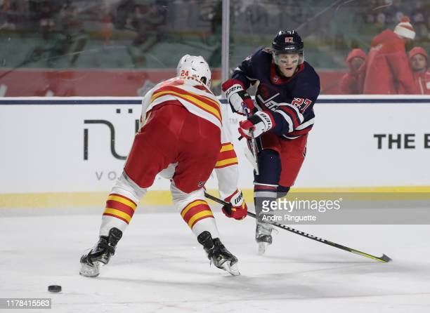 Nikolaj Ehlers of the Winnipeg Jets fires a shot with Travis Hamonic of the Calgary Flames defending during the 2019 Tim Hortons NHL Heritage Classic...