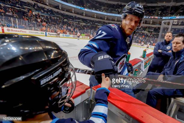 Nikolaj Ehlers of the Winnipeg Jets gives a first bump to the Toyota Trainer of the Day following the pregame warm up prior to NHL action against the...