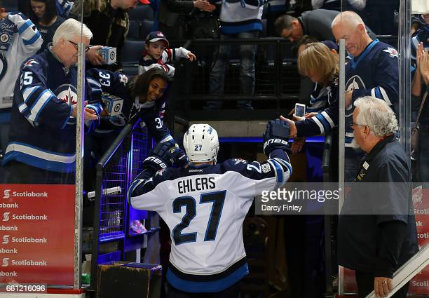 Nikolaj Ehlers of the Winnipeg Jets high fives fans as he heads off the ice after receiving first star honors following a 43 victory over the Anaheim...