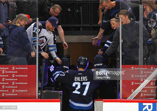 Nikolaj Ehlers of the Winnipeg Jets high fives the fans as he leaves the ice following a 52 victory over the Arizona Coyotes at the MTS Centre on...