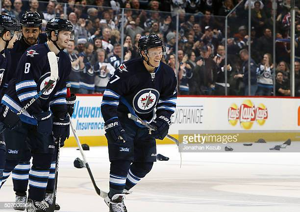 Nikolaj Ehlers of the Winnipeg Jets is all smiles as hats rain down from the stands following his first career hat trick during second period action...