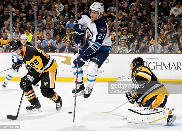 Nikolaj Ehlers of the Winnipeg Jets lumps against MarcAndre Fleury of the Pittsburgh Penguins at PPG Paints Arena on February 16 2017 in Pittsburgh...