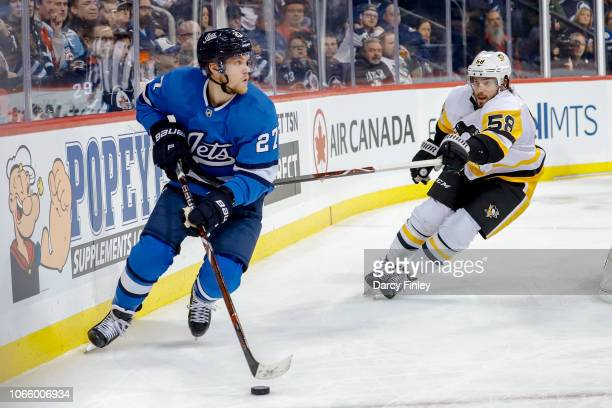 Nikolaj Ehlers of the Winnipeg Jets plays the puck along the boards as Kris Letang of the Pittsburgh Penguins gives chase during second period action...