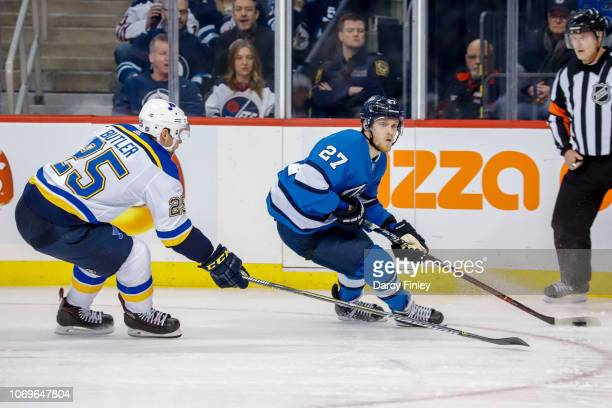 Nikolaj Ehlers of the Winnipeg Jets plays the puck down the ice as Chris Butler of the St Louis Blues gives chase during third period action at the...