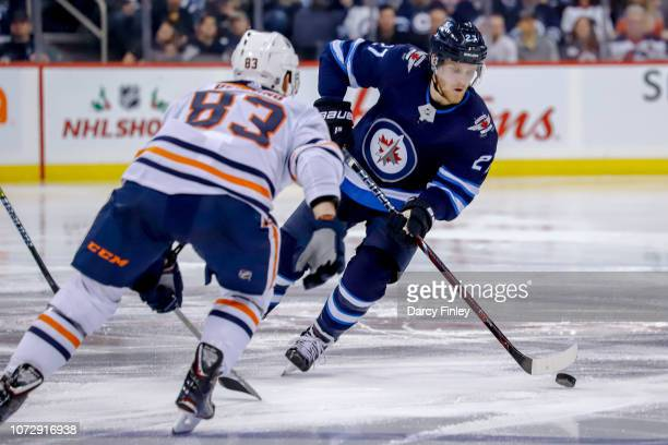 Nikolaj Ehlers of the Winnipeg Jets plays the puck down the ice as Matt Benning of the Edmonton Oilers defends during second period action at the...