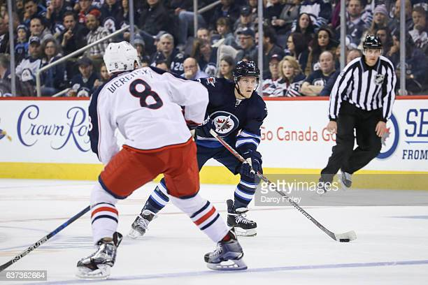 Nikolaj Ehlers of the Winnipeg Jets plays the puck up the ice as Zach Werenski of the Columbus Blue Jackets defends during first period action at the...