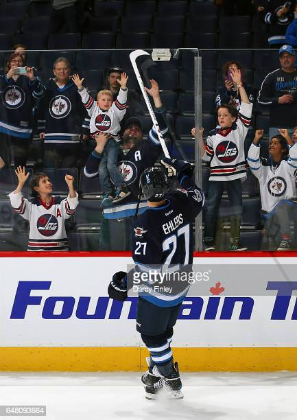 Nikolaj Ehlers of the Winnipeg Jets sends a souvenir stick over the glass to lucky fans following a 61 victory over the Colorado Avalanche at the MTS...