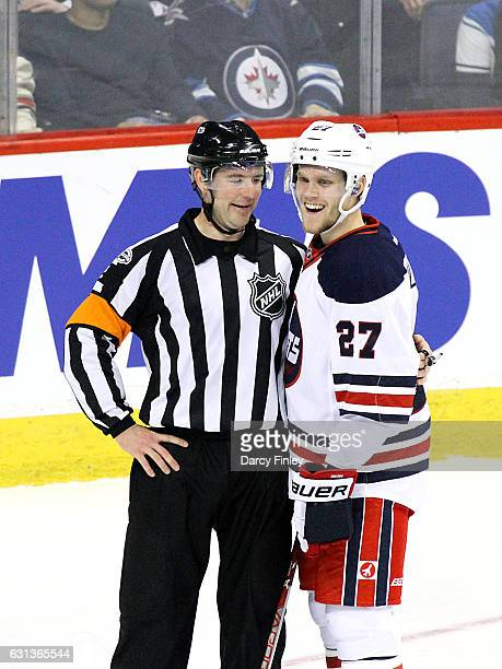 Nikolaj Ehlers of the Winnipeg Jets shares a laugh with referee Jon McIsaac during a second period stoppage in play against the Calgary Flames at the...