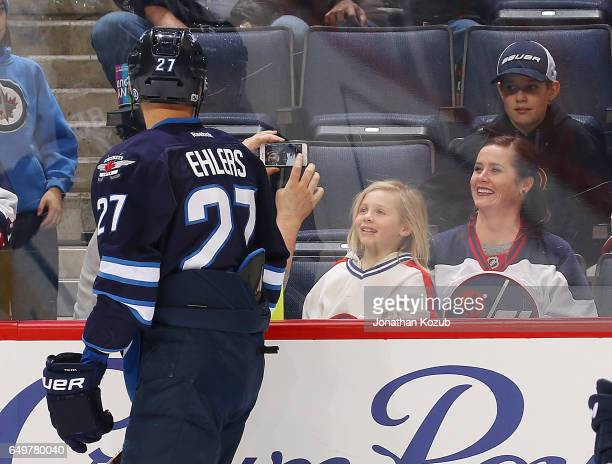 Nikolaj Ehlers of the Winnipeg Jets stops for a picture with a fan during the pregame warm up prior to NHL action against the Pittsburgh Penguins at...