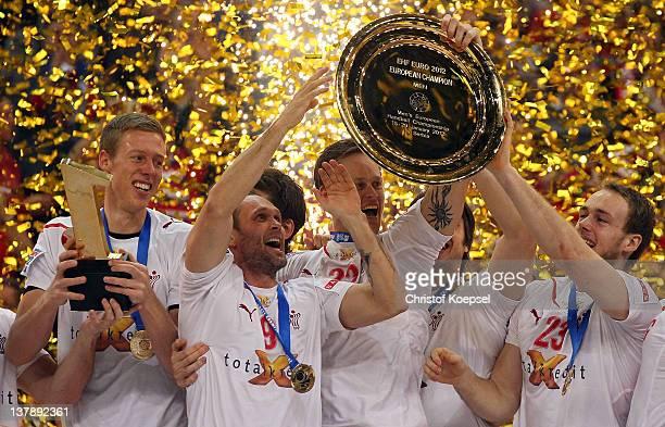 Nikolaj Markussen, Lars Christiansen, Kasper Soendergaard Sarup and Henrik Toft Hansen of Denmark lift up the EHF trophy on the podium after winning...