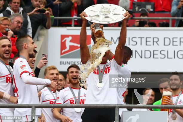 Nikolas Nartey of FC Koeln gets a beer shower as he celebrates with the Second Bundesliga trophy at the end of the Second Bundesliga match between 1....