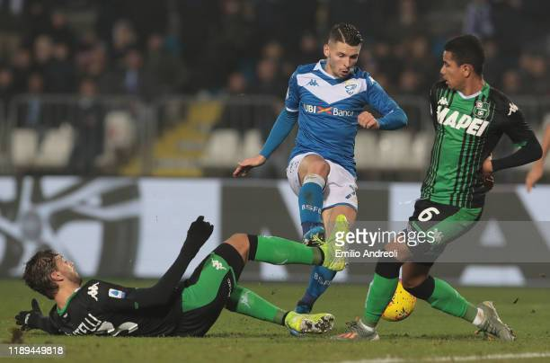 Nikolas Spalek of Brescia Calcio is challenged by Manuel Locatelli and Rogerio of US Sassuolo during the Serie A match between Brescia Calcio and US...