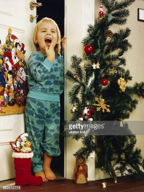 Ein Kind freut sich morgens über den mit Süßigkeiten gefüllten Stiefel vom Nikolaus An der Tür hängt ein Adventskalender an den Türrahmen ist ein...