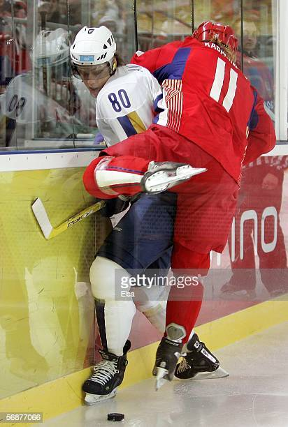 Nikolay Antropov of Kazakhstan is checked by Darius Kasparaitis of Russia during the first period of the men's ice hockey Preliminary Round Group B...