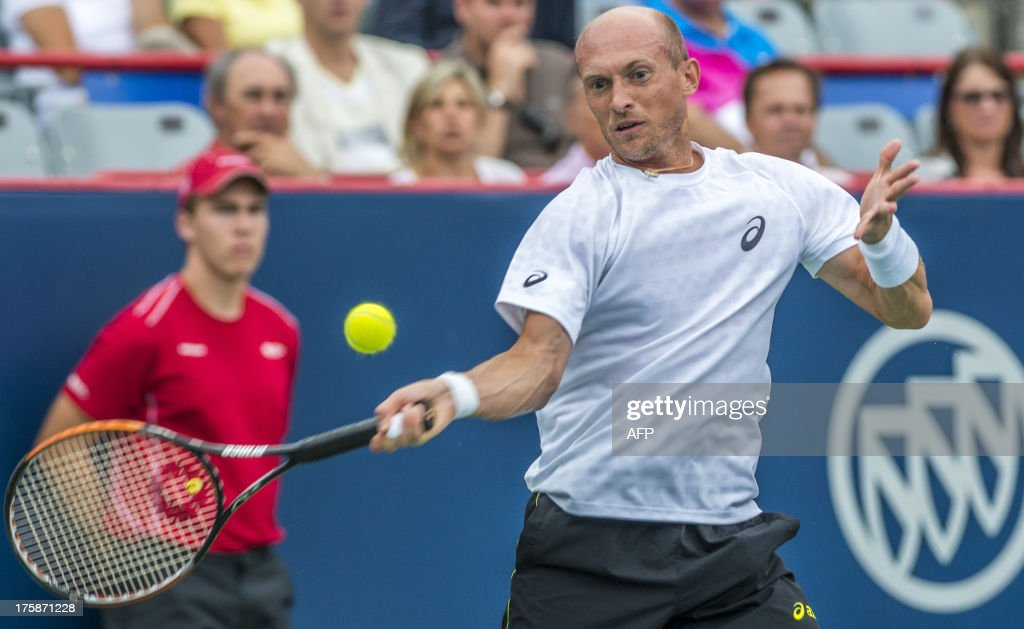 Nikolay Davydenko of Russia returns the ball to Vasek Pospisil of Canada during their quarterfinal match at the Uniprix Stadium during the Rogers Cup on August 9, 2013 in Montreal.