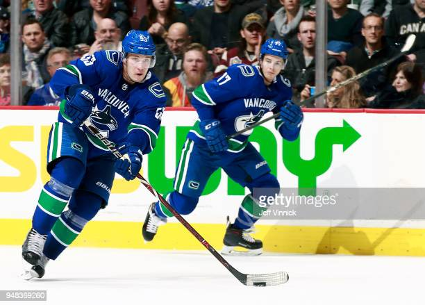 Nikolay Goldobin loos on as Bo Horvat of the Vancouver Canucks skates up ice with the puck during their NHL game against the Edmonton Oilers at...