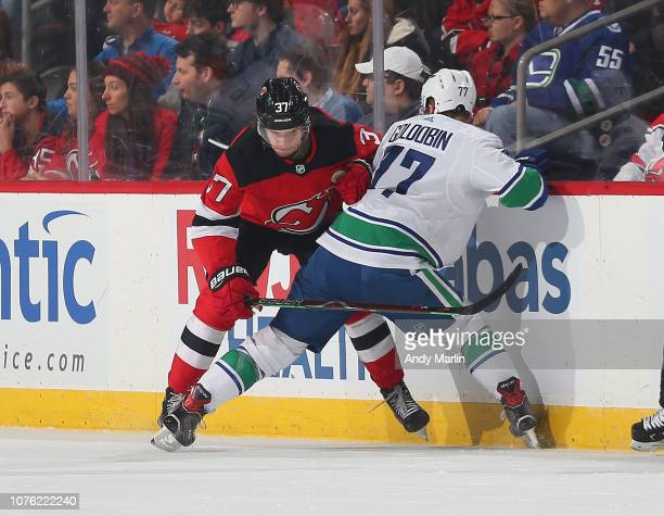 Nikolay Goldobin of the Vancouver Canucks and Pavel Zacha of the New Jersey  Devils battle for 01efd0196