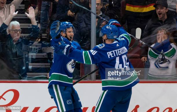 Nikolay Goldobin of the Vancouver Canucks celebrates with teammate Elias Pettersson after scoring a goal against the Calgary Flames in NHL action on...