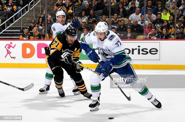 Nikolay Goldobin of the Vancouver Canucks handles the puck against Evgeni Malkin of the Pittsburgh Penguins at PPG Paints Arena on October 16 2018 in...