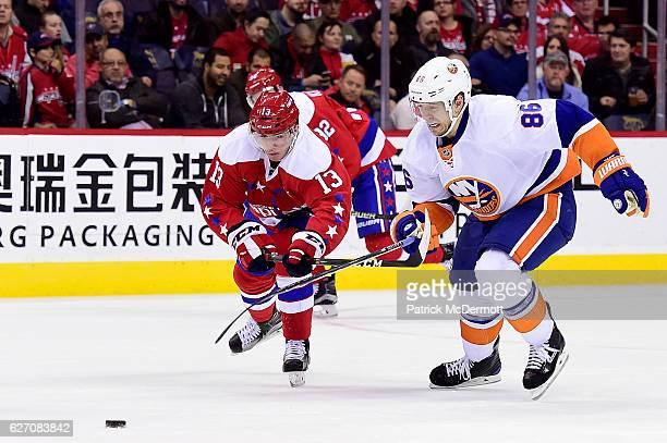 Nikolay Kulemin of the New York Islanders and Jakub Vrana of the Washington Capitals battle for the puck in the third period during a NHL game at...
